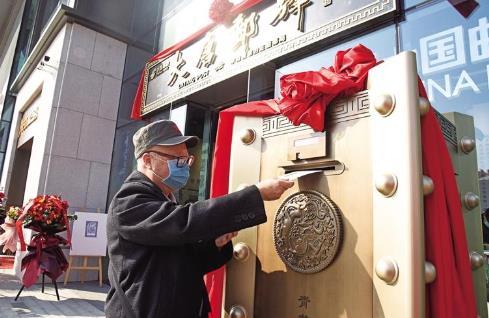 """2月8日,""""来自唐朝的邮局""""大唐邮驿主题邮局在西安市大唐不夜城开业。因疫情不能团聚,一位老人将一封写给远方亲人的信投入大唐邮驿主题邮局的铜匦·四兽信筒。.jpg"""